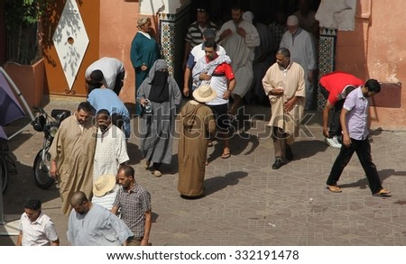 MARRAKESH, MOROCCO - OCTOBER 7: Local Muslim men coming out of the Koutoubia Mosque in the Jemaa El Fnaa square in Marrakesh, Morocco on the 7th October, 2015. - stock photo