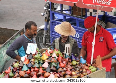 MARRAKESH, MOROCCO - OCTOBER 8: Locals selling tajine dishes in the Jemaa el Fna Square in Marrakesh, Morocco on the 8th October, 2015. - stock photo