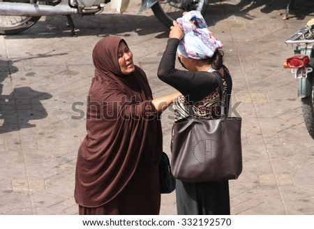 MARRAKESH, MOROCCO - OCTOBER 7: Two local Muslim women in traditional dress talking in Jemaa El Fnaa square in Marrakesh, Morocco on the 7th October, 2015. - stock photo
