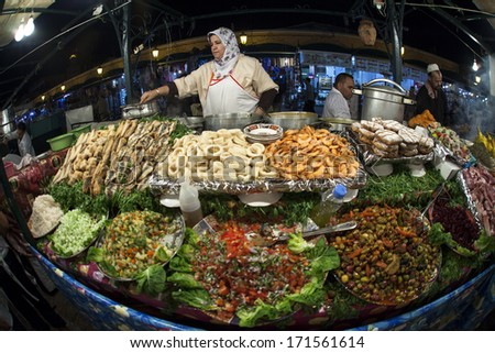 MARRAKESH ,MOROCCO - OCTOBER 8: Unidentified people selling food at night at the Djemaa el Fna square in Marrakesh on October 8, 2013 in Morocco. Every night the square turns into open air restaurant. - stock photo
