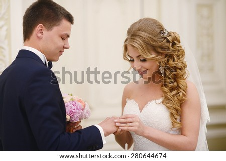 Marriage ceremony. Beautiful sexy model girl in white dress. Wedding couple. Man in suit. Beauty blonde bride with brunette groom. Female and male portrait. Woman with lace veil. Cute lady and guy - stock photo