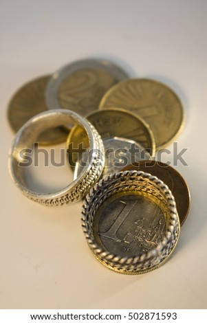 Marriage for Money Two wedding rings and coins that symbolize the people who get married for money and interest