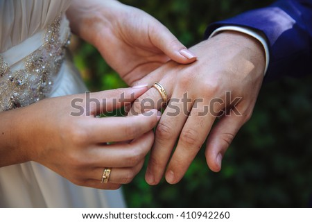 marriage hands with rings. birde wears the ring on the finger of the groom - stock photo