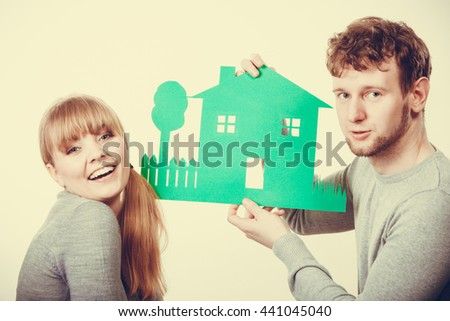 Marriage home love ownership property design concept. Cheerful pair celebrating their future. Young girlfriend boyfriend laughing preparing house model for family. - stock photo