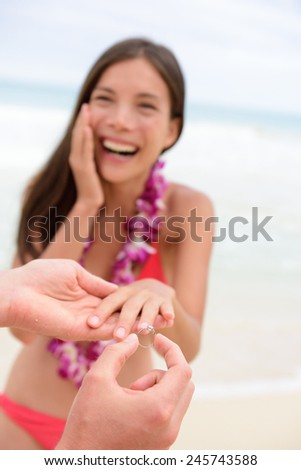 Marriage proposal casual couple beach wedding concept. Man proposing to girlfriend during holiday travel. Young lovers in love. - stock photo