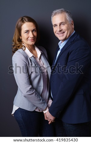 Married business partners smile and hold hands while standing face to face against a dark blue background - stock photo