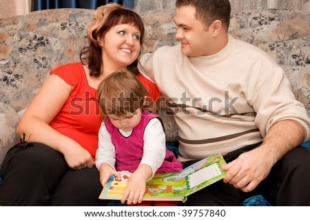 Married couple and  little girl read  book in a cozy room - stock photo