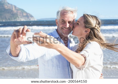 Married couple at the beach together taking a selfie on a sunny day - stock photo
