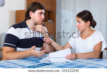Married couple counting family budget sitting at desk with documents