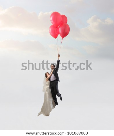Married couple flying with some balloons - stock photo