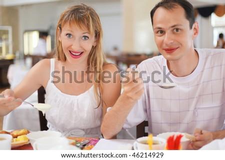 Married couple having breakfast at restaurant, eating cream wheat - stock photo
