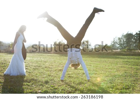 Married couple having fun on a field. The groom is jumping for joy. - stock photo