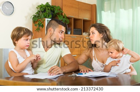 Married couple having quarrel in front of children at home - stock photo