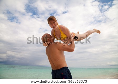 Married couple. Husband and wife. young man holds woman with red hair. yellow swimsuit bikini. Beach. White sand. Ocean. Sea. Blue water. Sky. Cloud. Joy. Crazy. Laugh. Smile. Gymnastics. Dance. Love
