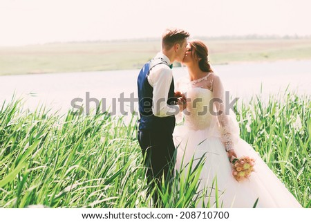 married couple kissing on nature