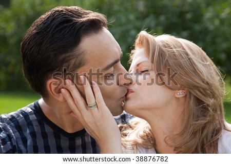 married couple kissing outdoors - stock photo