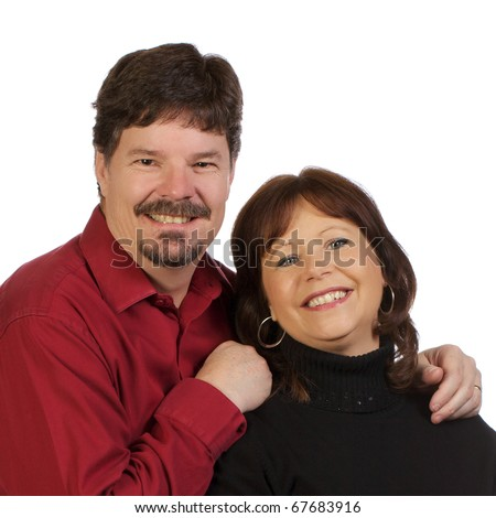 Married couple poses for camera with happy smiles on their faces.