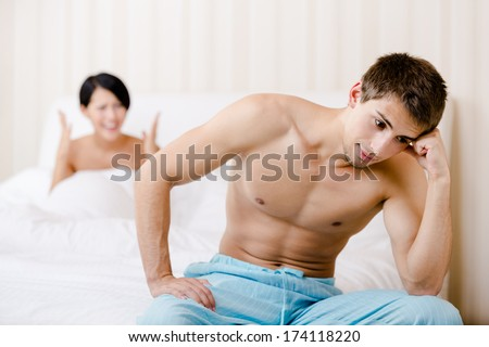 Married couple quarrels in bed. Depressed man sitting on the edge of the bed, focus on man - stock photo