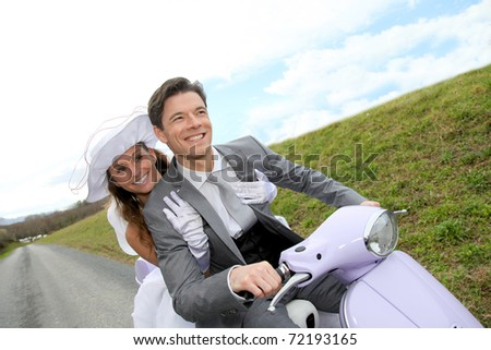 Married couple riding motorcycle on their wedding day - stock photo