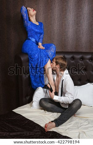 Married couple. Romantic evening at the hotel. Love and passion. Man kisses his wife's leg.
