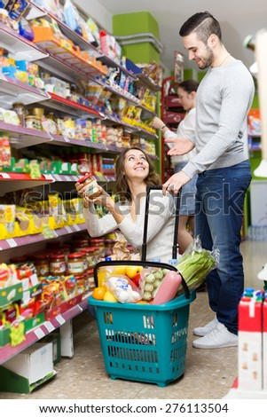 Married couple shopping for food in a supermarket. Husband is holding a full basket while wife is showing him canned vegetables - stock photo