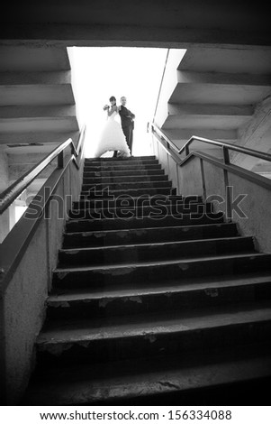 Married couple standing on top of stairs - stock photo