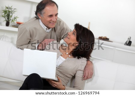 Married couple using laptop - stock photo