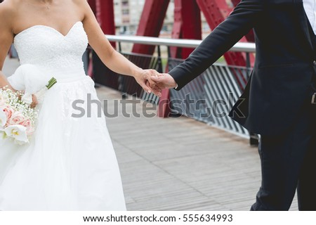 Married couple with ceremony dress walking on a red iron bridge. Close-up view of married couple's hands