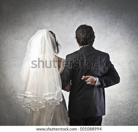 Married couple with infidel husband crossing his fingers behind his back - stock photo