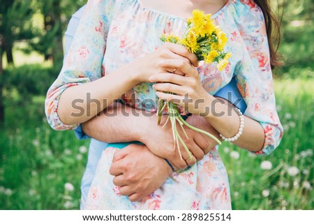 Married loving couple resting in summer, man embraces a woman in summer park. Woman holding bouquet of yellow dandelions - stock photo