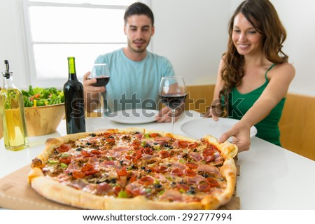 Married or engaged couple having a high calorie pizza lunch or dinner celebrating their relationship at a party - stock photo