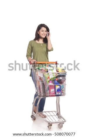Married woman with shopping cart talking on mobile phone