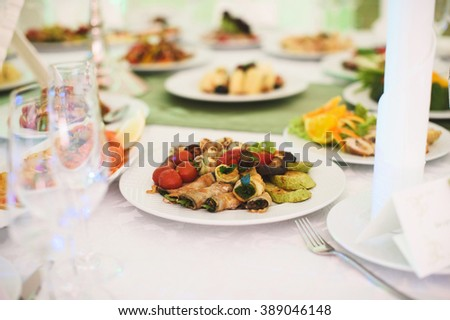 marrow rolls with small tomatoes at table - stock photo