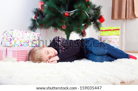 marry cristmas, little boy sleeping on the flor under the cristmas tree