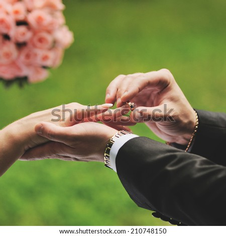 Marry me. Groom put a ring on finger of his lovely wife.  - stock photo