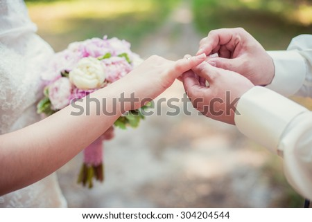 Marry me today and everyday, hands of a wedding heterosexual couple. Groom put a ring on finger of his lovely wife.  - stock photo