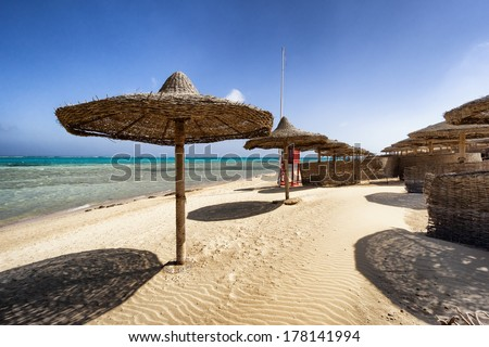 Marsa Alam beach with row of umbrella, Egypt - stock photo