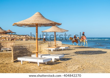 MARSA ALAM, EGYPT, MARCH 31, 2016: Female tourist  rides on camel on seashore of Red Sea accompanied by local guide on horse - stock photo
