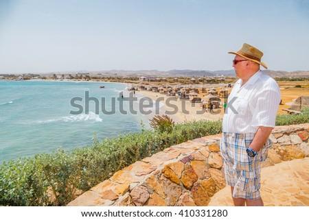 MARSA ALAM, EGYPT, MARCH 27, 2016: Senior tourist enjoys a beautiful sea view on Three Corners Equinox Beach Hotel terrace in Marsa Alam, Egypt - stock photo