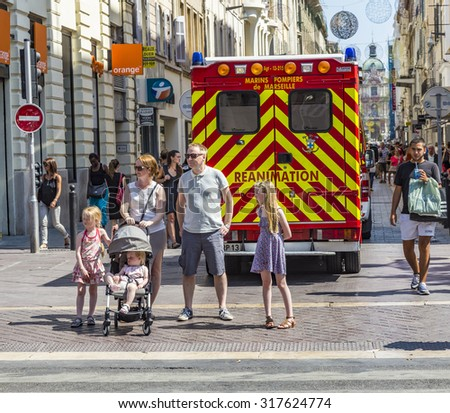 MARSEILLE, FRANCE - JULY 10, 2015: family waits at the sideway to cross the street. An ambulance car with reanimation parks in the pedestrian street. - stock photo