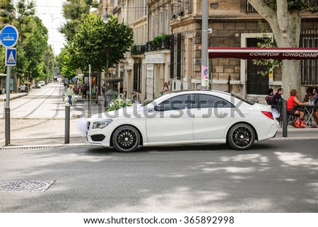 MARSEILLE, FRANCE - JULY 19, 2014: Mercedes-Benz limousine car decorated for a wedding parked near a bar waiting for the bride and groom as people drinks their coffee at the nearby bar
