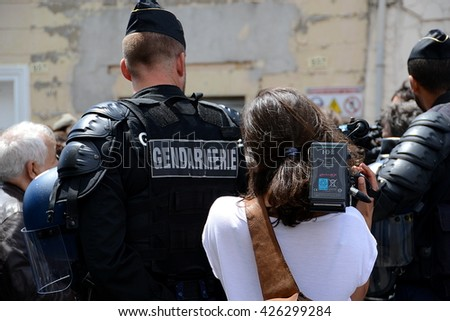 Marseille, France - May 23, 2016 : Woman from TV filming protesters behind the police during a demonstration to protest against the government's planned labor reforms - stock photo