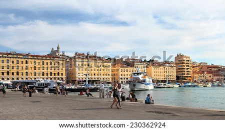 MARSEILLE - JULY 2, 2014: Old port (Vieux-Port) with people walking along the promenade and basilica of Notre-Dame-de-la-Garde on July 2, 2014, Marseille.