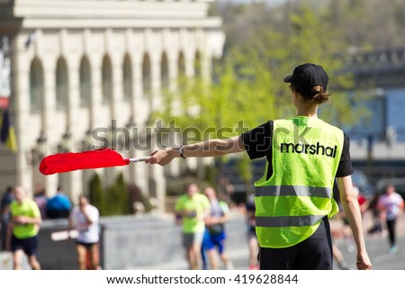 Marshal holds a flag in his hand and points in city marathon runners