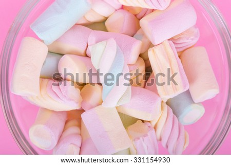 marshmallow candies of different colors in the glass on the background of pink. top view. entertainment for children in celebration.
