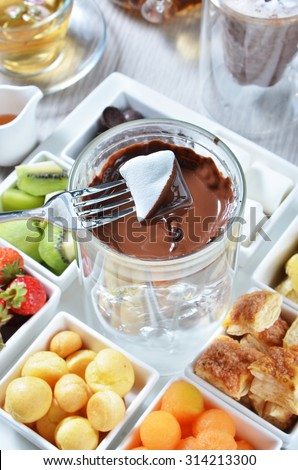 Marshmallow dipped in delicious melted chocolate fondue. - stock photo