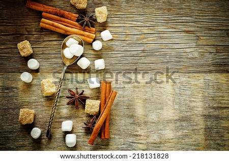 marshmallow with cinnamon, star anise and cane sugar on a dark wood background. tinting. selective focus on marshmallows in the spoon - stock photo