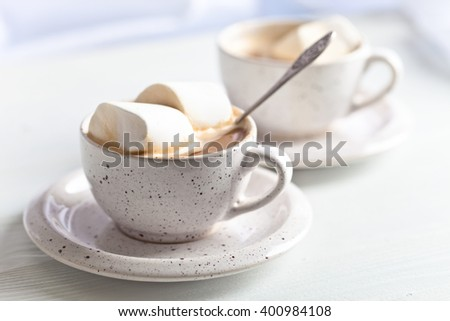 marshmallows and a cup of latte on a white wooden table