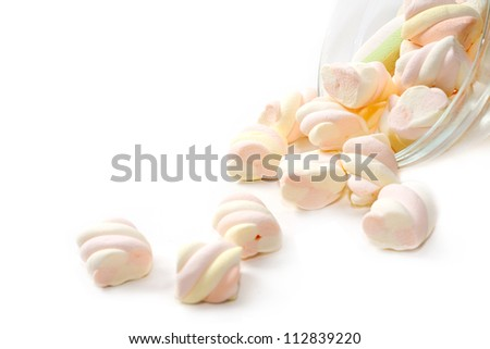 Marshmallows fall out of the bowl on white background - stock photo
