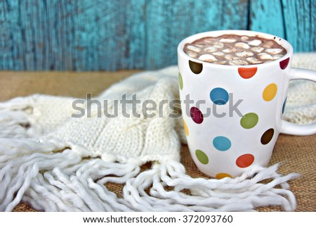 marshmallows in hot chocolate drink with knit winter scarf on burlap - stock photo